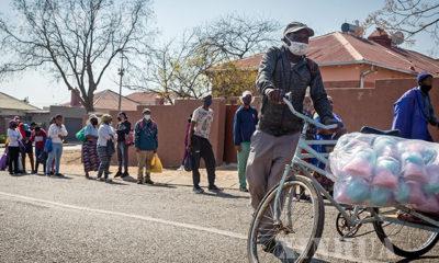 တောင်အာဖရိက နိုင်ငံသားများက နှာခေါင်းစည်းတပ်၍ အခမဲ့ပေးဝေနေသည့် အစားအသောက်များအား တန်းစီ စောင့်ဆိုင်းနေစဉ်(ဆင်ဟွာ)