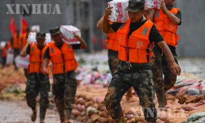 တရုတ်နိုင်ငံ ကျန်းရှီးပြည်နယ် ဖောရန်ခရိုင်အနီးရှိ ရေကာတာပေါ်တွင် အကာအရံတည်ဆောက်ကာ ရေလွှမ်းမိုးမှု ထိန်းချုပ်ရေးလုပ်ငန်းများ၌ ပါဝင်ကူညီပေးနေသော လူငယ်ရဲတပ်ဖွဲ့ဝင်များအား တွေ့ရစဉ် (ဆင်ဟွာ)