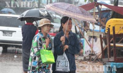 မိုးရေထဲတွင် ထီးဖြင့် သွားလာနေကြသူများအားတွေ့ရစဉ် (ဆင်ဟွာ)
