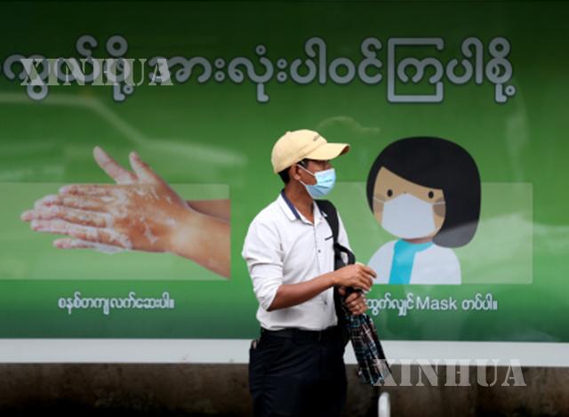 ရန်ကုန်မြို့ရှိ ဘတ်စ်ကားမှတ်တိုင် တစ်ခုတွင် နှာခေါင်းစည်း တပ်ဆင်ထားသူ တစ်ဦးအား တွေ့ရစဉ်(ဆင်ဟွာ)
