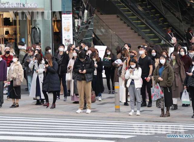 ဂျပန်နိုင်ငံ တိုကျိုမြို့ရှိ မီးနီနေသော မီးပွိုင့်တစ်ခုရှေ့တွင် လမ်းဖြတ်ကူးရန်စောင့်ဆိုင်းနေသည့် နှာခေါင်းစည်းတပ်ဆင်ထားသူများကို တွေ့ရစဉ် (ဆင်ဟွာ)