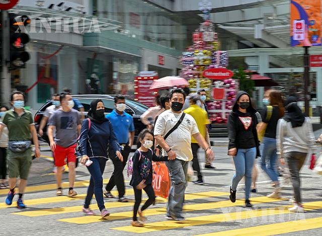 မလေးရှားနိုင်ငံ ကွာလာလမ်ပူမြို့တွင် ဒီဇင်ဘာ ၂၈ ရက်က လူများ နှာခေါင်းစည်းတပ်၍ သွားလာနေသည်ကို မြင်တွေ့ရစဉ်(ဆင်ဟွာ)