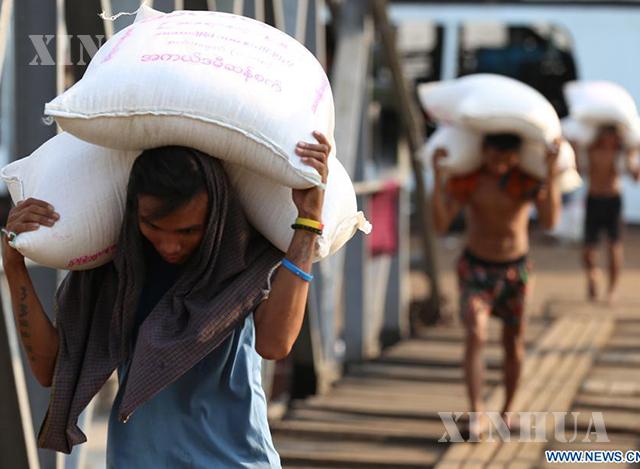 ရန်ကုန်မြို့ရှိ ဆိပ်ကမ်းတစ်ခု၌ ဆန်အိတ်ထမ်းနေသော အလုပ်သမားများအား တွေ့ရစဉ်(ဆင်ဟွာ)
