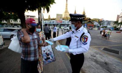 ရန်ကုန်မြို့တွင် သွားလာနေသူများအား နှာခေါင်းစည်းများ ဝေငှပေးနေသည်ကို တွေ့ရစဉ်(ဆင်ဟွာ)