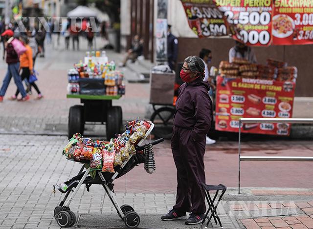 ကိုလံဘီယာနိုင်ငံမြို့တော် ဘိုဂိုတာ တွင် နှာခေါင်းစည်းတပ်၍ ဈေးရောင်းနေသူ တစ်ဦးအား မြင်တွေ့ရစဉ်(ဆင်ဟွာ)