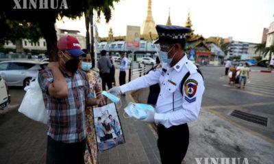 ယာဉ်ထိန်းရဲတစ်ဦးမှ ပြည်သူများအား နှာခေါင်းစည်း ဝေပေးနေစဉ် (ဆင်ဟွာ)