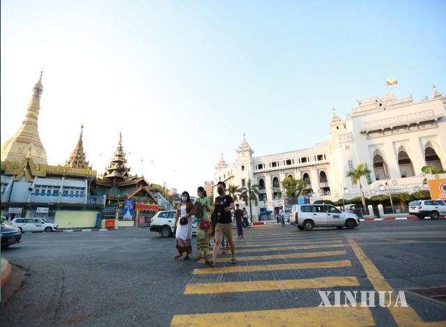 မြန်မာနိုင်ငံ ရန်ကုန်မြို့ရှိ မြို့တော်ခန်းမအနီး လမ်းဖြတ်ကူးနေသူများကို တွေ့ရစဉ် (ဆင်ဟွာ)